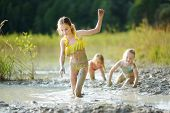 Three Young Sisters Taking Healing Mud Baths On Lake Gela Near Vilnius, Lithuania. Children Having F poster
