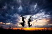 Couple Silhouette Jumping At Sunset