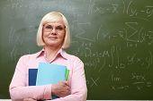 Porträt von ausgereift Lehrer mit Blick in die Kamera mit Tafel auf Hintergrund copybooks