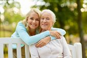 family, generation and people concept - happy smiling young daughter with senior mother sitting on p poster
