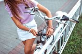 Close-up, A Girl In Summer In City, Puts Lock On Her Bike, Protection Against Theft, Bicycle Parking poster
