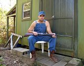 stock photo of hillbilly  - Angry looking young man in old overalls seated and holding a shotgun outside a cabin or hunting camp - JPG