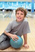 niño feliz sonriente se sienta en el piso con la bola azul en el club de bowling