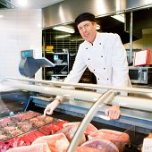 A butcher at a fresh meat counter or deli in a store