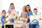 Cute Little Children With Teacher Showing Their Paintings At Lesson Indoors poster