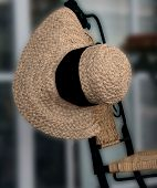 View of A Boutique Window With Empasis On The Straw Hat Draped On A Wrought Iron Chair