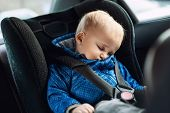 Cute Caucasian Toodler Boy Sleeping In Child Safety Seat In Car During Road Trip. Adorable Baby Drea poster