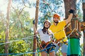 Young Beauty Female Woman Adult Wears Protective Helmet Having Fun In Extreme Rope Park, Amusement P poster