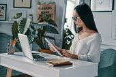 Working Hard. Beautiful Young Woman Working Using Digital Tablet While Sitting In Home Office poster