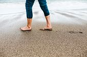 Barefoot Girl In Jeans Walking Along The Sandy Shore. poster