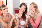 Three female friends drinking wine on sofa