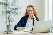 Photo Of Successful Ginger Female Freelancer Has Remote Work, Watches Webinar Online On Laptop Compu poster