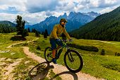 Single mountain bike rider on electric bike, e-mountainbike rides mountain trail. Man cycling on bik poster