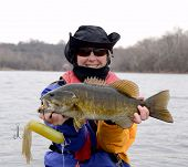 A Large Brown And Bronze Smallmouth And A Large Tube Jig Bass Being Held Horizontally By A Woman In  poster