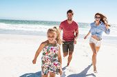 Happy family playing on the beach. Beautiful daughter running on the beach with mother and father in poster
