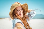 Portrait of beautiful mature woman in casual wearing straw hat at seaside. Cheerful young woman smi poster