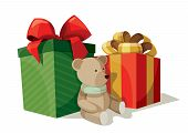 Two boxes of presents with a teddy bear sitting nearby