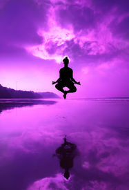 picture of samadhi  - Woman Silhouette doing yoga padmasana lotus posture in jumping on the beach at the sunset in purple color - JPG