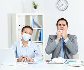 Image of sick businessman with tissue sneezing with his colleague in mask sitting near by and lookin