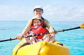 Madre e hijo, kayak en el mar tropical