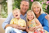stock photo of grandparent child  - Grandparents And Grandchildren Sitting On Sofa Together - JPG