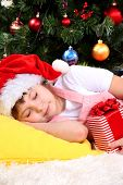 The little girl fell asleep with gift in their hands in festively decorated room