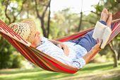 Senior Man relaxante em rede com o livro