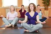 Grupo de mulheres fazendo exercícios de ioga relaxante no ginásio