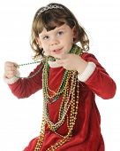 An adorable preschooler in her red velvet Christmas dress happily wearing oodles of Christmas beads.
