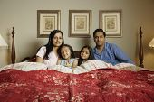 Portrait of family sitting in bed