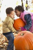 stock photo of brother sister  - Brother and sister lifting pumpkin - JPG