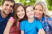 stock photo of youngster  - Photo of happy family of four looking at camera outdoors - JPG