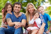 stock photo of youngster  - Photo of happy family looking at camera outdoors - JPG