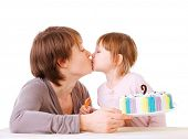 Little daughter kissing her mother. torte