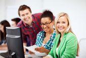 educação, tecnologia e internet - alunos com computador estudando na escola