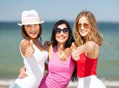 summer holidays and vacation - group of girls showing thumbs up on the beach