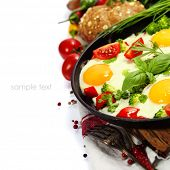 Fried eggs with fresh vegetables over white (health, breakfast or vegetarian concept)
