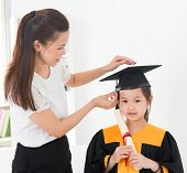 Asian child graduation, teacher adjusting cap for student indoor.