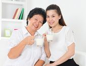 Drinking milk. Happy Asian family drinking milk at home. Beautiful senior mother and adult daughter, healthcare concept.
