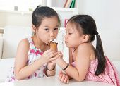 Eating ice cream cone. Asian children sharing an ice cream at home.  Beautiful girls model.