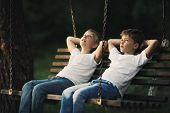 little boys riding on a swing