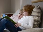 image of storytime  - Side view of two young sisters reading book on a bed - JPG
