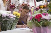 Young female florist at work with many flowers