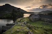 Beautiful Image Of Stone Barn With Mountains And Lake At Sunrise