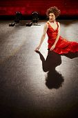 Beautiful young woman in red gown sitting on stage floor