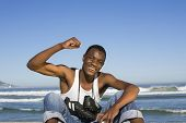 Portrait of a smiling man with football boots round neck cheering on beach