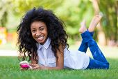 Teenage Black Girl Using A Phone, Lying On The Grass - African People