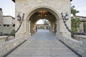 Stone gateway with arched structure to modern home