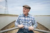 Senior man rowing a boat on a reservoir