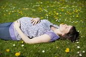 Side view of a pregnant young woman lying on grass